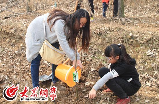母女俩为树苗浇水.jpg